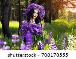 Small photo of Carefree adolescence. Portrait of young, attractive tattooed woman with wreath on head keeping bouquet of violet flowers in hands and looking down while standing on the garden.