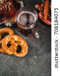 Small photo of Selection of traditional German food Oktoberfest. Beer, baked pork shank, popcorn, assortment of different sausages, homemade bretzels. On a black stone background copy space top view