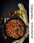 Small photo of Chicken liver (offal) with onions and tomatoes in a frying pan in Armenian. Flat lay. Top view