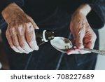 elderly woman pours medicine in ... | Shutterstock . vector #708227689