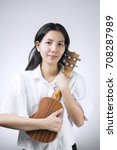 Small photo of portraits Female Musician who embraces his favorite musical instruments cherish on white background.