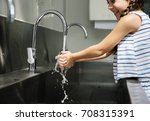 Young Girl Washing Hands With...