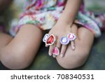 Small photo of Children's hand with a lot of toy rings