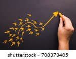 Small photo of Hand draw a curve arrow leader with many small follower on chalkboard