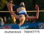 woman jumping over bar at... | Shutterstock . vector #708447775
