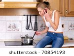 Young attractive woman cooks soup while talking phone - stock photo