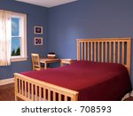 Beautiful bedroom with blue walls and a red bedspread. - stock photo