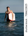 Teenage boy with a body board in the sea - stock photo