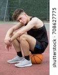 Teenage boy sitting on a basketball on a court looking sad - stock photo