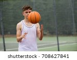Teenage boy tossing a basketball from one hand to another on a court - stock photo