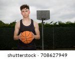 Teenage boy holding a basketball on a court - stock photo