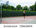Teenage boy shooting a basketball on a court - stock photo