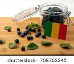 Small photo of Malian flag on a wooden plank with blueberries isolated on white
