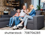 smiling young family with two... | Shutterstock . vector #708706285