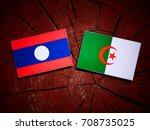 Small photo of Laos flag with Algerian flag on a tree stump isolated