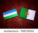 Small photo of Uzbekistan flag with Algerian flag on a tree stump isolated