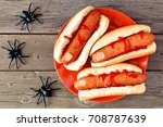 Creepy Halloween hot dog fingers on an orange plate over a rustic old wood background