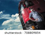 Proud Trucker and His Truck. Caucasian Trucker with Euro Semi Tractor Closeup Photo - stock photo