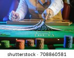 Small photo of Professional croupier during cards shuffle in the casino