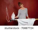 young woman ironing a shirt - stock photo