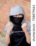 Young caucasian teenage boy in handcuffs after being arrested - stock photo