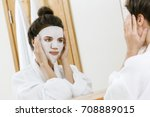 woman is applying sheet mask on ... | Shutterstock . vector #708889015