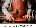 barman holds a cocktail with... | Shutterstock . vector #708936115