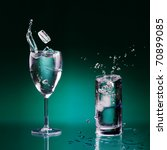 two clear glasses of water standing on wet surface and few pieces of ice dropped with splashes and bubbles - stock photo