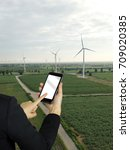 Small photo of Business woman touching phone screen at wind turbine farm park generation with air flow spinning blades. Clean renewable green wind power concept.