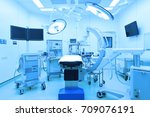 Small photo of equipment and medical devices in modern operating room take with art lighting and blue filter