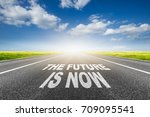 Small photo of the future is now written on asphalt road.Concept for success and passing time.