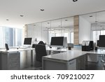 Open space office environment with wooden, white and glass walls, rows of white computer desks and original ceiling lamps. 3d rendering mock up