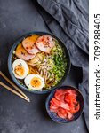 Small photo of Traditional Japanese soup ramen with meat broth, asian noodles, seaweed, sliced pork, eggs and ginger on dark concrete background. Close up. Asian style food. Top view. Hot tasty ramen soup for dinner