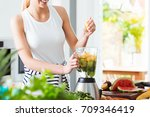 woman making fruit cocktail in... | Shutterstock . vector #709346419