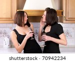 Two pretty female have an argument in the home kitchen - stock photo