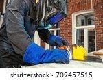 a welder  dressed in black work ... | Shutterstock . vector #709457515
