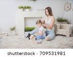 mother combing daughter's hair | Shutterstock . vector #709531981