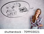 Small photo of Attractive smiling young woman dreaming of wealth on concrete background. Rich concept