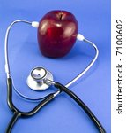 Small photo of An apple and stethoscope arranged in an effort to depict an old familiar adage.