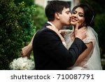 groom kisses bride's cheek... | Shutterstock . vector #710087791