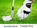 hand putting golf ball on tee... | Shutterstock . vector #710087941