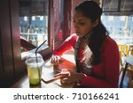 young woman with drink using... | Shutterstock . vector #710166241