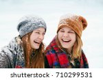 two happy young women in snow | Shutterstock . vector #710299531