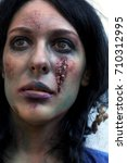 Small photo of young zombie girl with traces of facial decomposition portrait