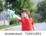 little boy playing with soap... | Shutterstock . vector #710411851
