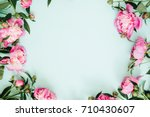 Stock photo frame wreath of pink peony flowers branches leaves and petals with space for text on blue 710430607