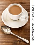 Small photo of cup of warm coffee with milk and sweetener on a spoon