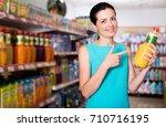 happy adult girl choosing fruit ... | Shutterstock . vector #710716195