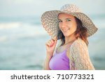 woman with big hat on the beach ... | Shutterstock . vector #710773321