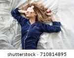 cute blonde in her bed in blue... | Shutterstock . vector #710814895